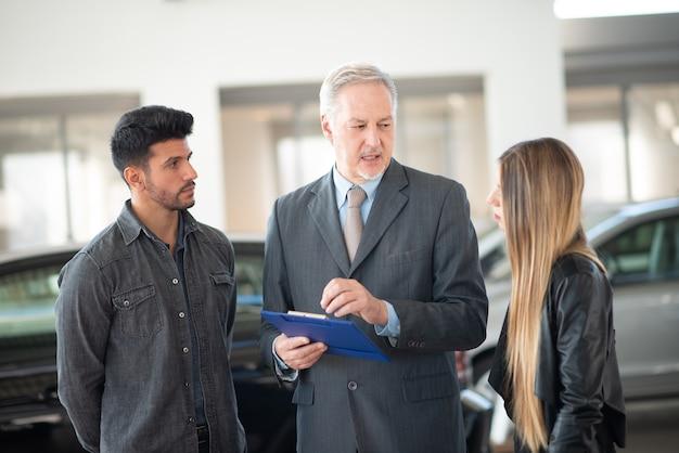 Szczęśliwa młoda rodzina rozmawia ze sprzedawcą i wybiera nowy samochód w salonie