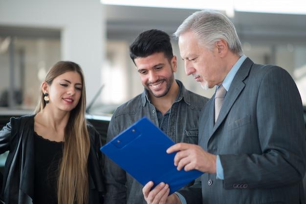 Szczęśliwa młoda rodzina rozmawia ze sprzedawcą w salonie samochodowym