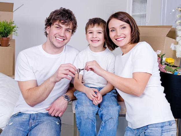 Szczęśliwa młoda rodzina siedzi w swoim nowym mieszkaniu