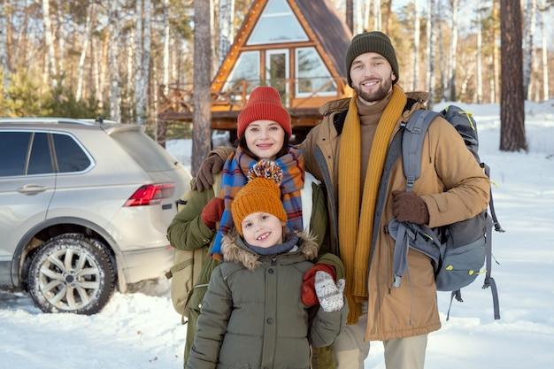 Szczęśliwa młoda rodzina składająca się z trzech osób w ciepłej odzieży zimowej, stojąca przed kamerą przed swoim wiejskim domem i patrząca na ciebie na zewnątrz