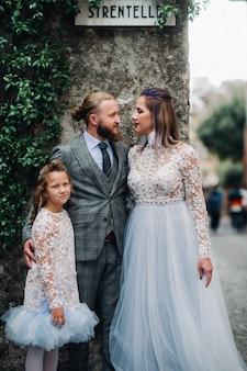 Szczęśliwa młoda rodzina spaceruje po starym mieście sirmione we włoszech.