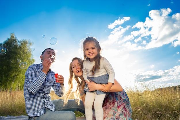 Szczęśliwa młoda rodzina spaceruje w przyrodzie, o zachodzie słońca