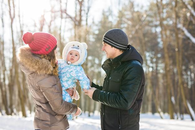 Szczęśliwa młoda rodzina spędza czas na świeżym powietrzu w zimie.