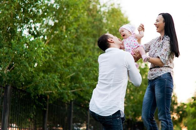 Szczęśliwa młoda rodzina spędza czas na zewnątrz w zielonej naturze