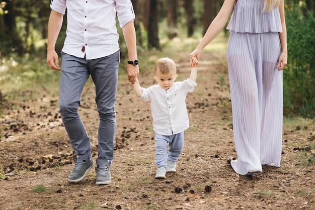Szczęśliwa młoda rodzina spędza czas w naturze. rodzice idą i trzymają dziecko za ręce
