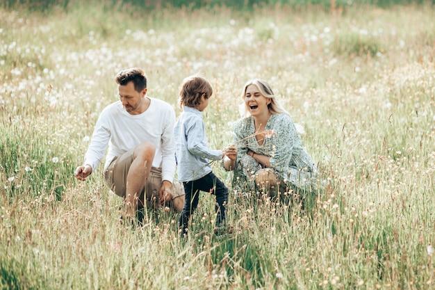 Szczęśliwa młoda rodzina spędzać czas razem na zewnątrz w zielonej łące z kwiatem na zewnątrz. pojęcie wakacji rodzinnych.