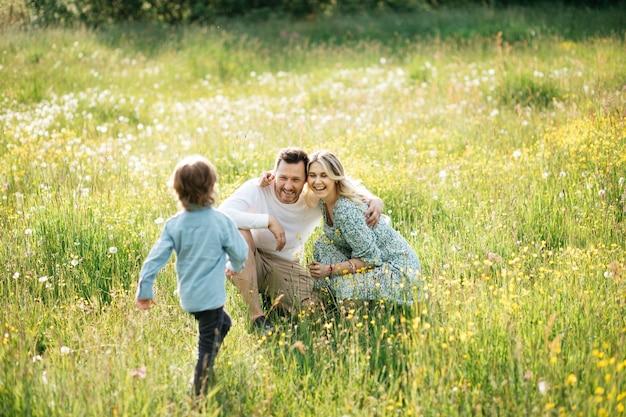 Szczęśliwa młoda rodzina spędzać czas razem na zewnątrz w zielonej łące z kwiatem na zewnątrz.