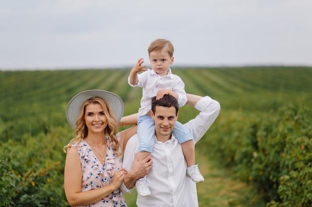 Szczęśliwa młoda rodzina tata, mama i synek wyglądają na szczęśliwych w parku