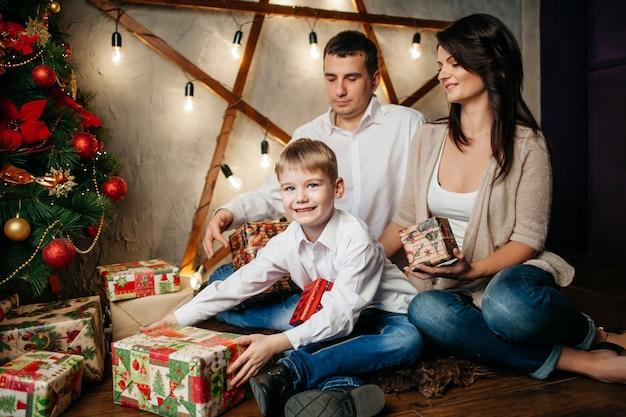 Szczęśliwa młoda rodzina w ozdoby świąteczne, mama, tata i mały chłopiec w pobliżu choinki z prezentami w pobliżu
