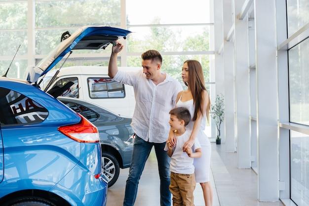 Szczęśliwa młoda rodzina w salonie samochodowym