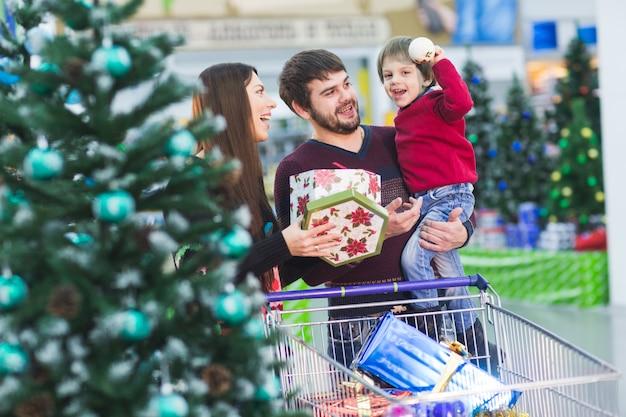Szczęśliwa młoda rodzina w supermarkecie wybiera prezenty na choinkę