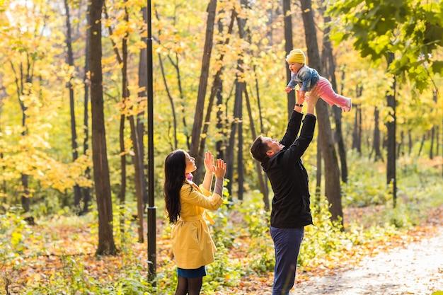 Szczęśliwa młoda rodzina z córką spędzając czas na świeżym powietrzu w jesiennym parku