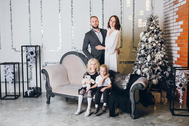 Szczęśliwa młoda rodzina z dwójką dzieci na choince