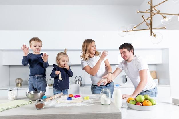 Szczęśliwa młoda rodzina z dwójką małych dzieci radośnie przygotowuje ciasteczka ciasta w kuchni. miłość i czułość w związku.