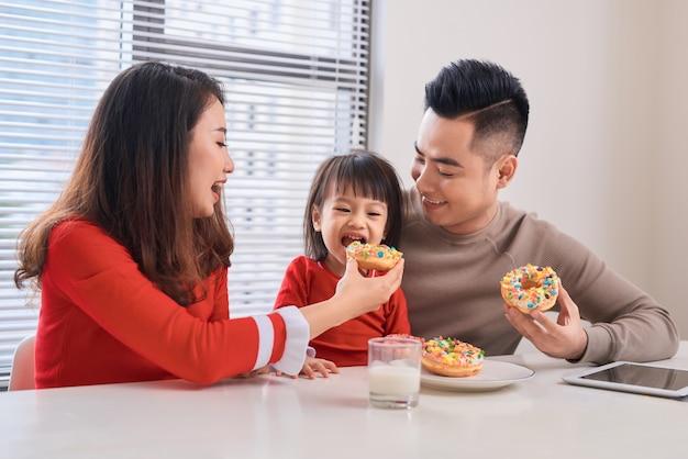 Szczęśliwa młoda rodzina z dziećmi jedząca śniadanie w białej słonecznej jadalni z dużym oknem z widokiem na ogród