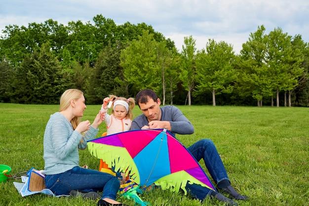 Szczęśliwa młoda rodzina z latającym latawcem w parku