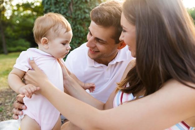 Szczęśliwa młoda rodzina z małą córeczką spędzającą razem czas