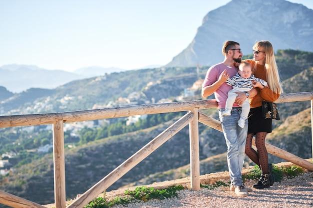 Szczęśliwa młoda rodzina z małą śliczną chłopiec cieszy się słonecznego dzień