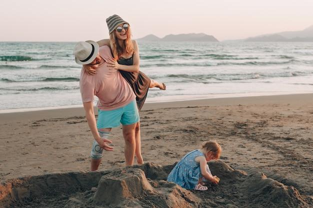 Szczęśliwa młoda rodzina z małym dzieckiem ma zabawę przy plażą. radosna rodzina.