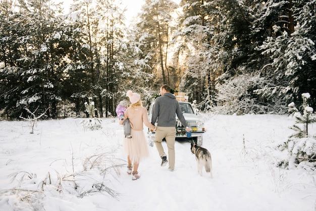 Szczęśliwa młoda rodzina z małym dzieckiem przygotowuje się do bożego narodzenia, spacerując z psem husky na tle retro samochodu, na dachu choinki i prezentów w zimowym śnieżnym lesie.