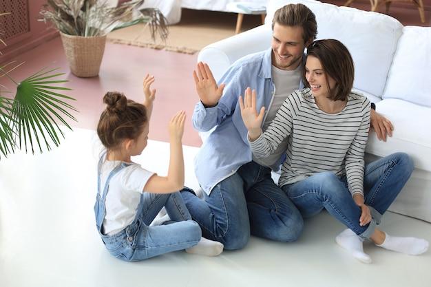 Szczęśliwa młoda rodzina z małym dzieckiem siedzi na ciepłej podłodze relaksując się razem, rozradowani rodzice odpoczywają weekend bawią się z małą córeczką, przybijają piątkę bawiąc się.