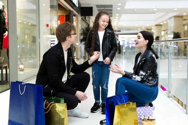 Szczęśliwa młoda rodzina z papierowymi torbami na zakupy w centrum handlowym