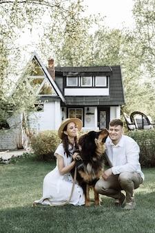 Szczęśliwa młoda rodzina z psem na nowy dom kupiony na hipotekę