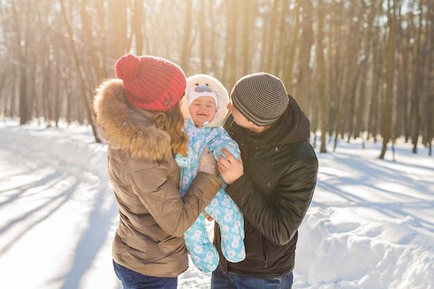 Szczęśliwa młoda rodzina z synkiem spędza czas na świeżym powietrzu w winter park.