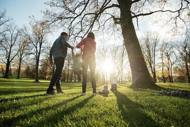 Szczęśliwa młoda rodzina z trójką dzieci bawiące się w parku jesienią