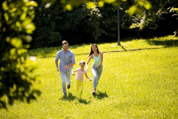 Szczęśliwa młoda rodzina z uroczą córeczką biegającą w parku w słoneczny dzień