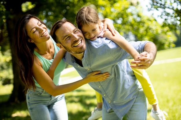 Szczęśliwa młoda rodzina z uroczą małą córeczką bawiącą się w parku w słoneczny dzień
