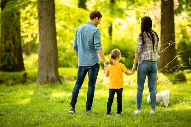 Szczęśliwa młoda rodzina z uroczym psem bichon w parku
