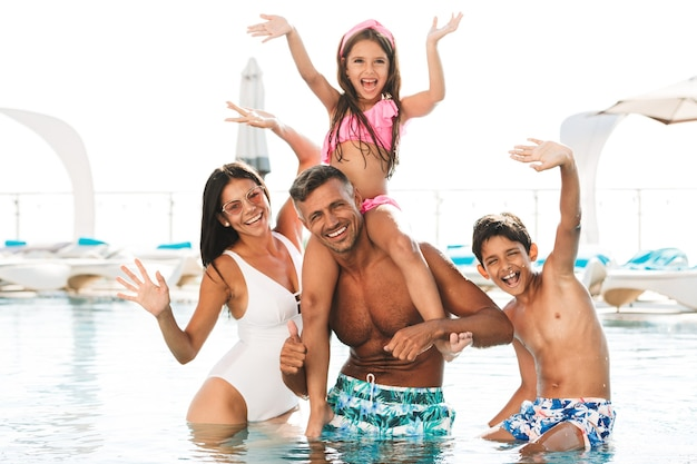 Szczęśliwa młoda rodzina zabawy w basenie