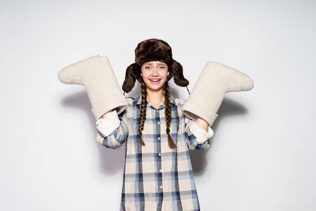 Szczęśliwa młoda rosjanka w kapeluszu z nausznikami trzyma ciepłe zimowe filcowe buty