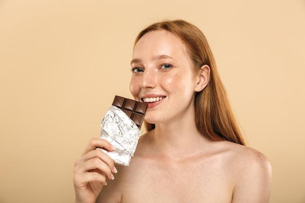 Szczęśliwa młoda ruda kobieta jedzenie czekolady. patrząc na aparat.