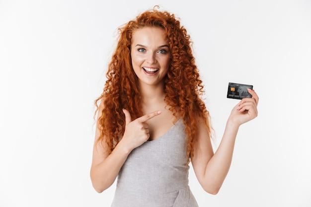 Szczęśliwa młoda ruda kręcone kobieta trzyma kartę kredytową.
