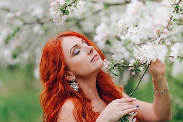 Szczęśliwa młoda rudowłosa kobieta stoi w kwitnącym sadzie jabłkowym, z bliska