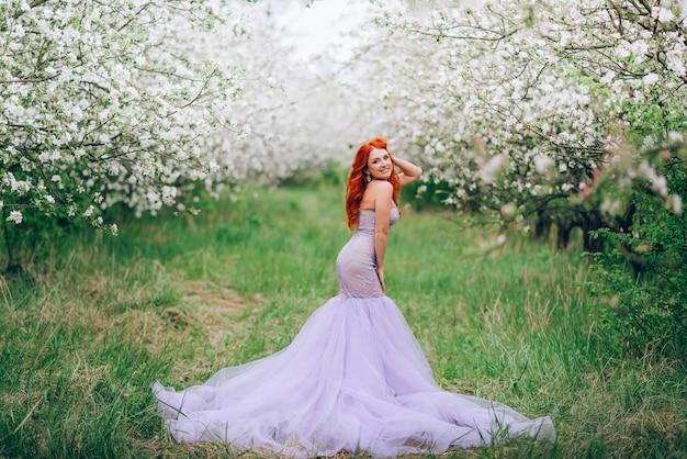 Szczęśliwa młoda rudowłosa kobieta stoi w sadzie kwitnących jabłoni, portret