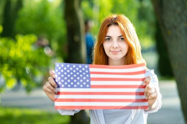 Szczęśliwa młoda rudowłosa kobieta trzyma flagę narodową usa w jej ręce na zewnątrz w lecie. pozytywna dziewczyna obchodzi dzień niepodległości stanów zjednoczonych.