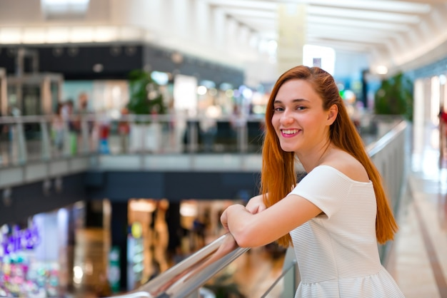 Szczęśliwa młoda rudzielec ładna dziewczyna w centrum handlowym
