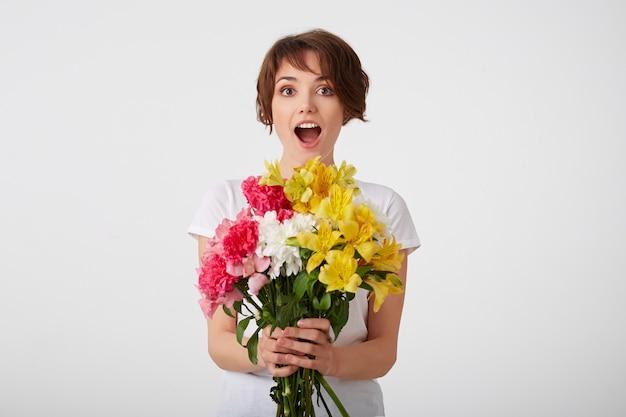 Szczęśliwa młoda śliczna krótkowłosa dziewczyna w białej pustej koszulce, z szeroko otwartymi ustami i oczami, trzymając bukiet kolorowych kwiatów, na białym tle nad białą ścianą.