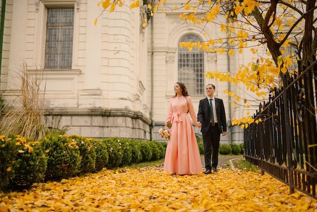 Szczęśliwa młoda ślub świeżo poślubiona para na spacerze w parku złoty złoty jesień jesień w pobliżu zabytkowej gotyckiej katedry atmosfera