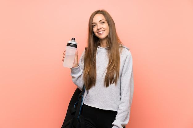 Szczęśliwa młoda sport kobieta nad odosobnioną menchii ścianą z butelką woda