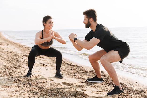 Szczęśliwa młoda sportowa para robi przysiady
