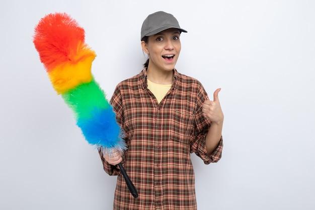 Szczęśliwa młoda sprzątaczka w zwykłych ubraniach i czapce, trzymająca kolorową miotełkę, uśmiechając się radośnie pokazując kciuki do góry stojąc na białym tle