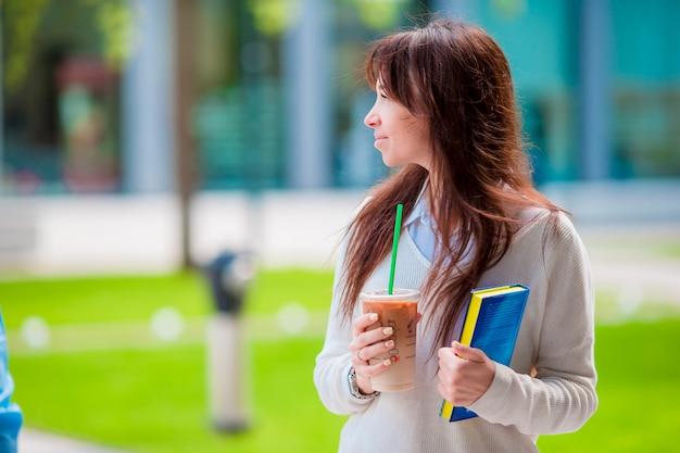 Szczęśliwa młoda studencka dziewczyna z kawą na wynos, chodzi w lato parku i trzyma książki dla czytać.