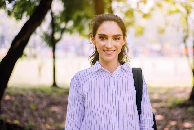 Szczęśliwa młoda studencka kobiety pozycja przy jawnym parkiem w ranku, szczęśliwa i uśmiechnięta