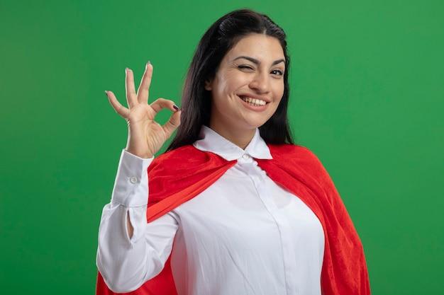 Szczęśliwa młoda superwoman w dobrym nastroju robi to w porządku znak i mruga patrząc na przód na białym tle na zielonej ścianie
