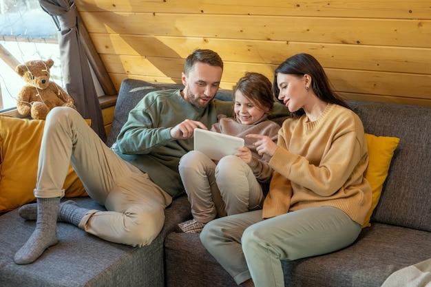 Szczęśliwa młoda trzyosobowa rodzina w stroju casual, siedząca na kanapie w wiejskim domu i oglądająca film online, wskazując na ekran tabletu