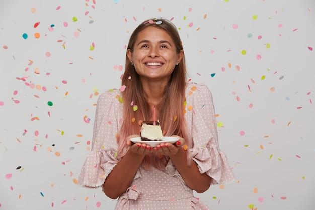 Szczęśliwa młoda urocza dama z jasnobrązowymi długimi włosami patrzy wesoło na bok, trzymając tort urodzinowy w dłoniach, życząc i ciesząc się z miłej imprezy, odizolowanej na białej ścianie